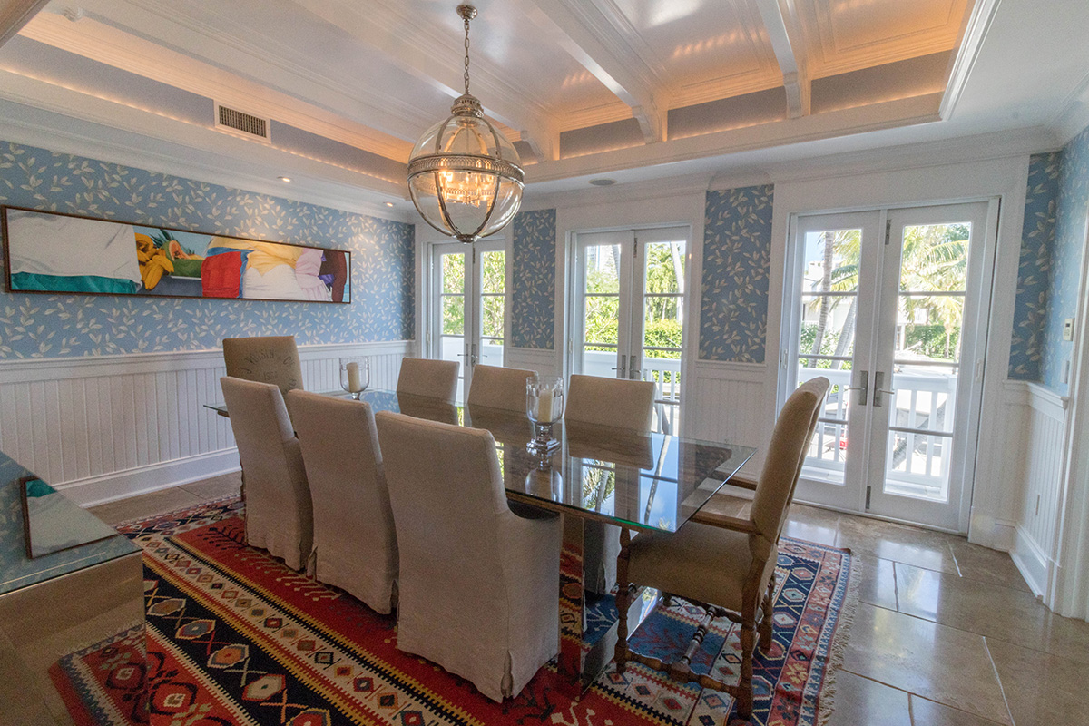 The formal dining room features walls of windows for natural illumination throughout. Entertain your guests in style and luxury as custom woodwork in the ceilings add to the luxury.